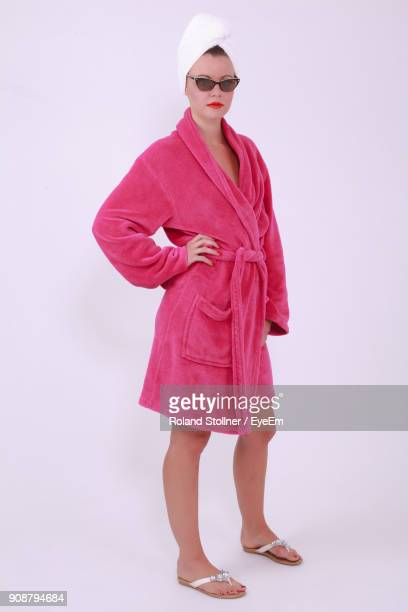 portrait of young woman in bathrobe standing against white background - bathrobe stock pictures, royalty-free photos & images