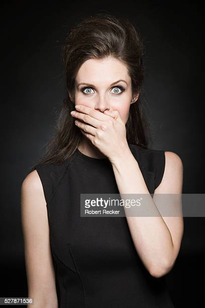 portrait of young woman in black dress - hands covering mouth stock pictures, royalty-free photos & images