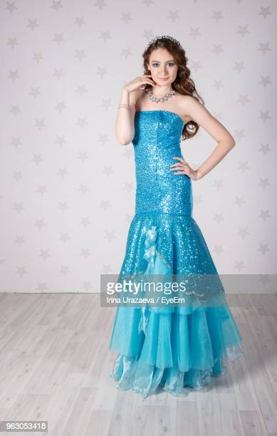 Portrait Of Young Woman In Blue Dress Standing Against Wall