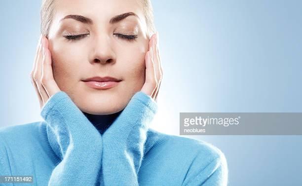 クローズアップの美しい若い女性の顔にブルーのセーター