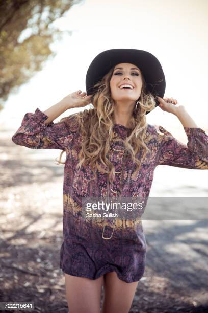 portrait of young woman in boho style and felt hat on roadside - shorts stock pictures, royalty-free photos & images