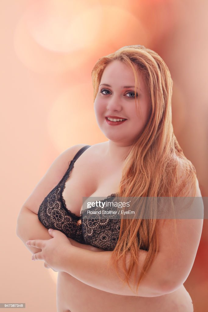 Portrait Of Young Woman In Bra Standing Against Colored Background : Stock Photo