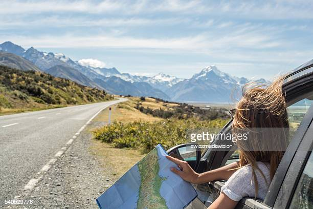 portrait of young woman in car looking at map - toerisme stockfoto's en -beelden
