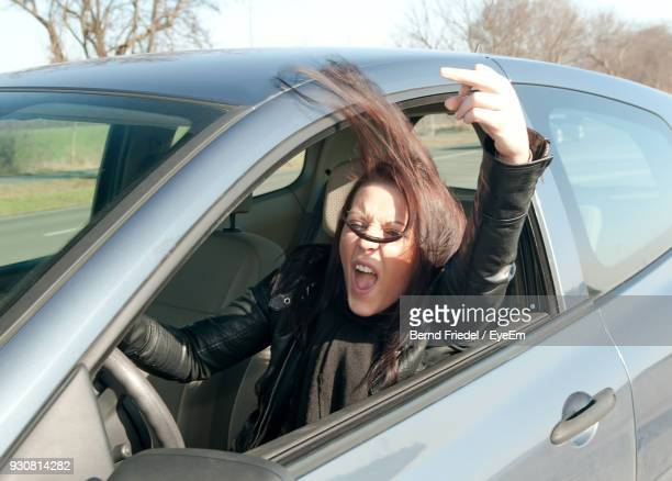 portrait of young woman in car showing obscene gesture - rasend vor wut stock-fotos und bilder