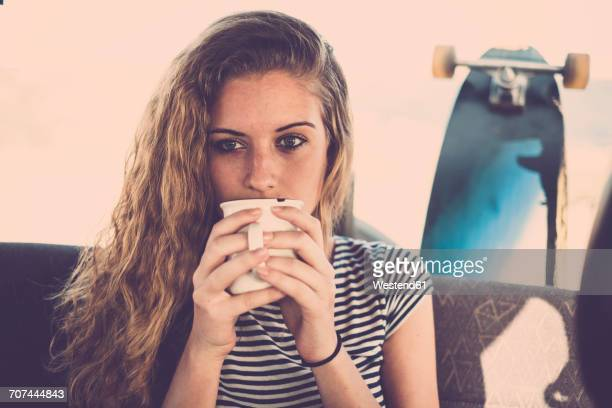 Portrait of young woman in car with cup of coffee