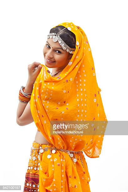 portrait of young woman in chaniya choli looking over shoulder against white background - dupatta stock pictures, royalty-free photos & images