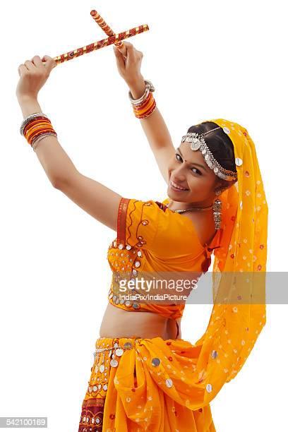 Portrait of young woman in chaniya choli performing Dandiya Raas over white background