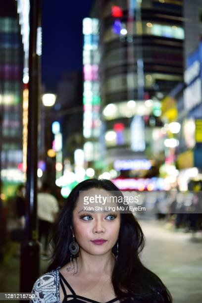 portrait of young woman in city - 歓楽街 ストックフォトと画像
