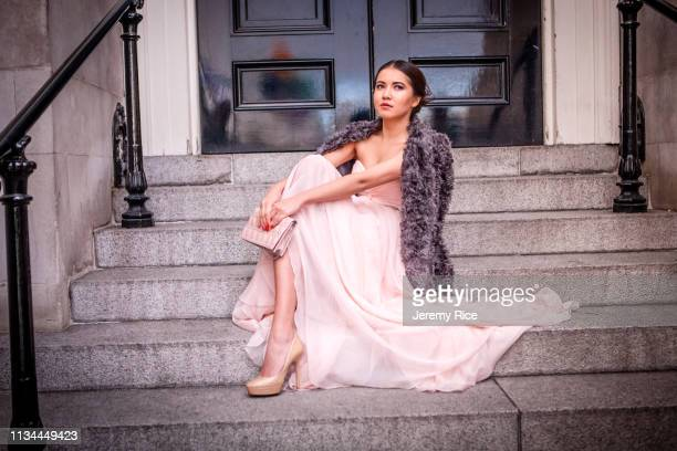 portrait of young woman in evening gown sitting on steps - vestido de noite - fotografias e filmes do acervo