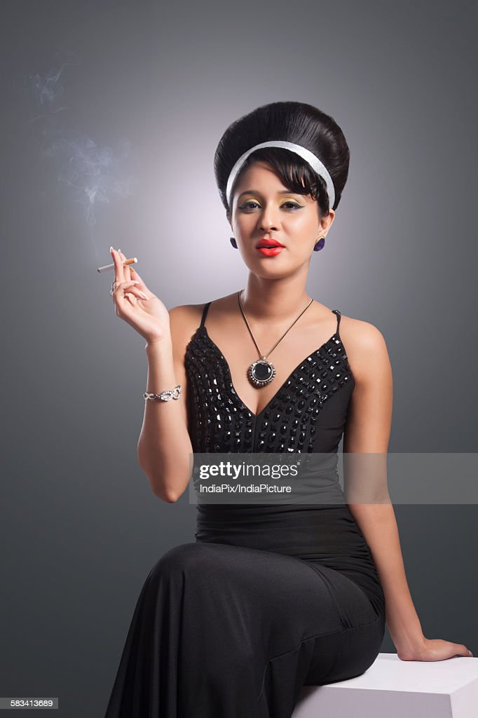 Portrait of young woman in evening gown smoking : Stock Photo