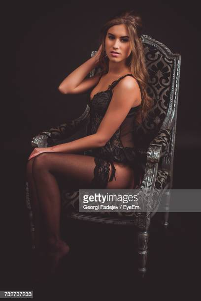 portrait of young woman in fetish wear sitting on armchair against black background - stockings no shoes stock photos and pictures