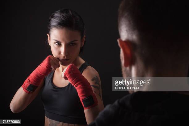 Portrait of young woman in fighting stance, facing fitness trainer