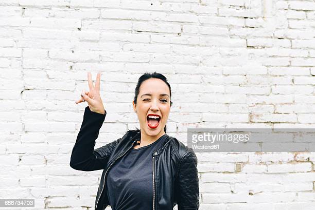portrait of young woman in front of brick wall making victory sign - blouson en cuir photos et images de collection