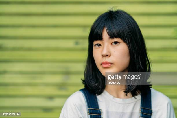 portrait of young woman in front of green wall - fringe stock pictures, royalty-free photos & images
