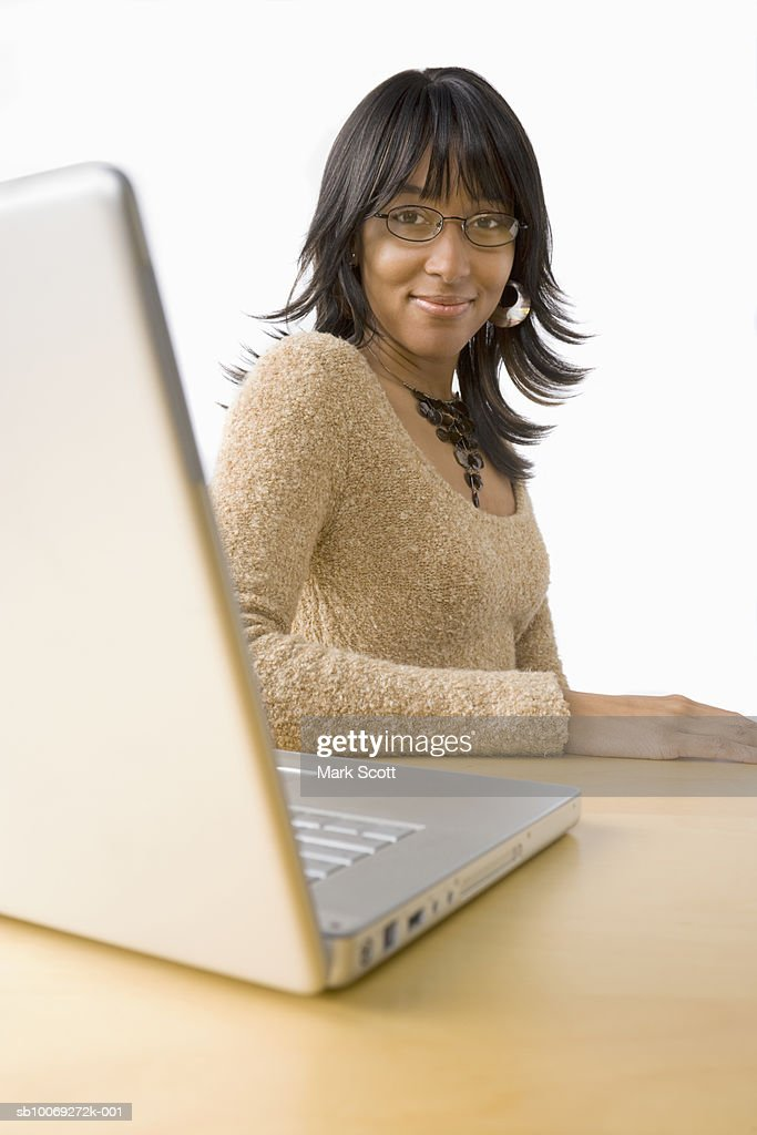 Portrait of young woman in front of laptop, smiling : Stockfoto