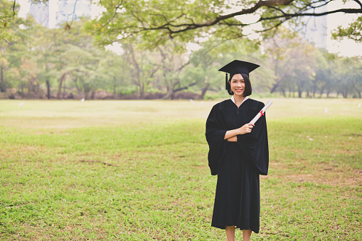 Portrait Of Young Woman In Graduation Gown Holding Certificate While Standing At Park - gettyimageskorea