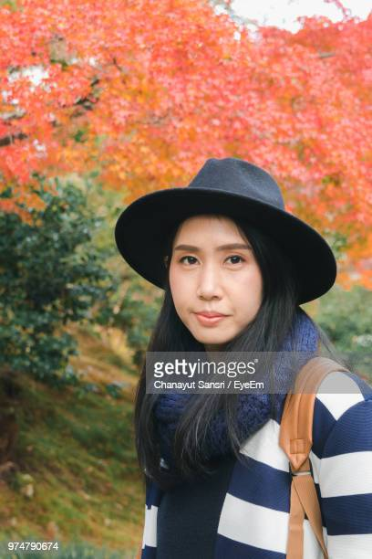 portrait of young woman in hat standing against trees - chanayut stock photos and pictures