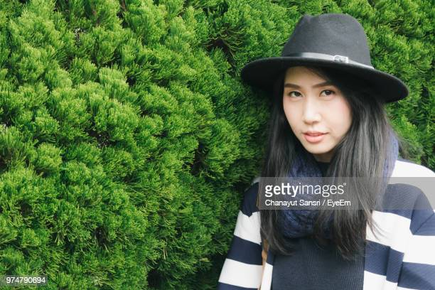 portrait of young woman in hat standing by trees - chanayut stock photos and pictures