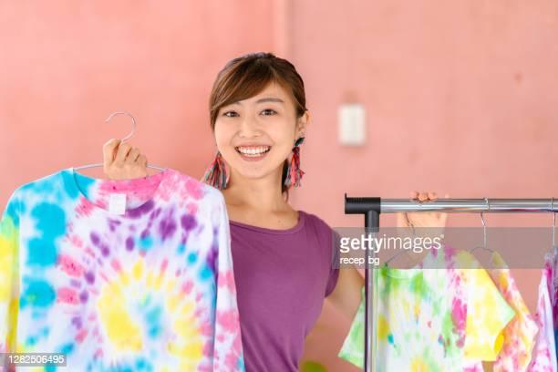 染めたウェアとショッピングバッグを持つ彼女のネクタイ染料スタジオで若い女性の肖像画 - タイダイ柄 ストックフォトと画像