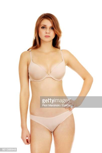 portrait of young woman in lingerie standing against white background - femmes en culottes photos et images de collection