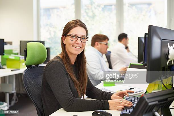 portrait of young woman in office - richard drury stock pictures, royalty-free photos & images