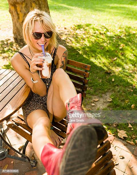 Portrait of young woman in park drinking frappe