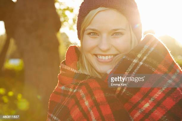 Portrait of young woman in park, tartan picnic blanket around shoulders