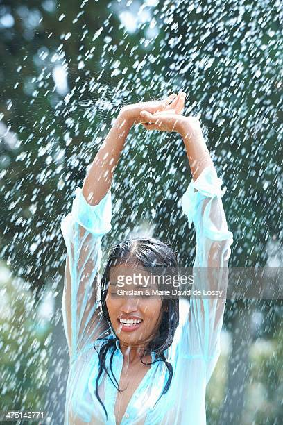 portrait of young woman in rain with arms raised - women in see through tops stock photos and pictures