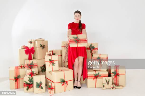 portrait of young woman in red dress by stacked christmas gifts handing christmas parcel - una sola mujer joven fotografías e imágenes de stock