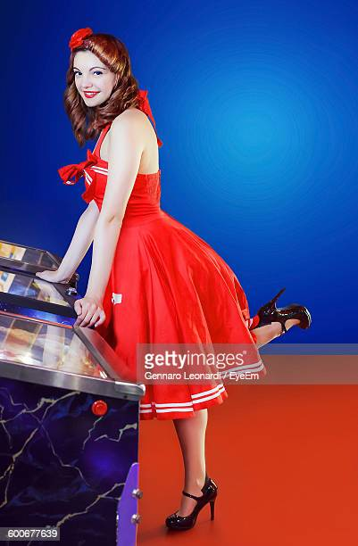 Portrait Of Young Woman In Red Dress Leaning On Pinball Machine