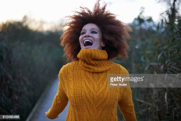 portrait of young woman in rural setting, laughing - big hair stock photos and pictures
