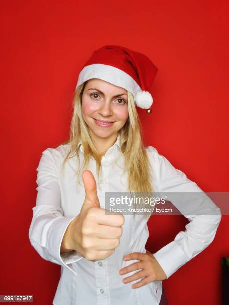 Portrait Of Young Woman In Santa Hat Showing Thumbs Up Against Red Background