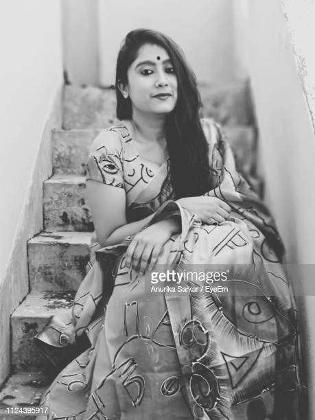 portrait of young woman in sari sitting on staircase - sari stock pictures, royalty-free photos & images