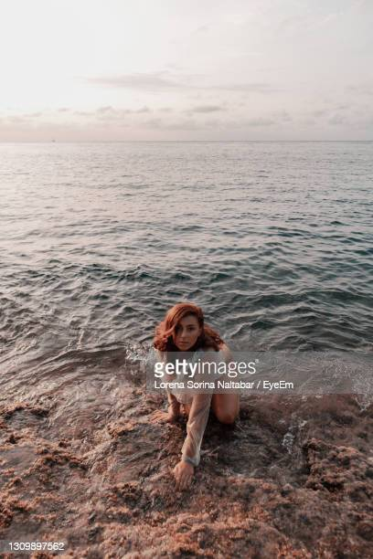 portrait of young woman in sea against sky - lorena day stock pictures, royalty-free photos & images