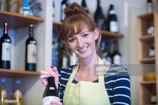 portrait of young woman in shop, holding bottle of wine - sigrid gombert stock-fotos und bilder