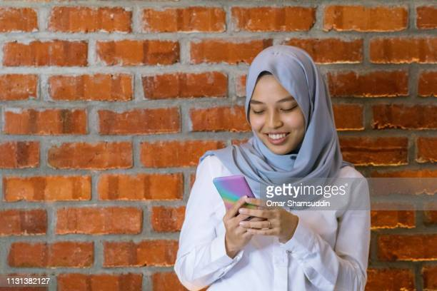Portrait of young woman in smart casual using smart phone