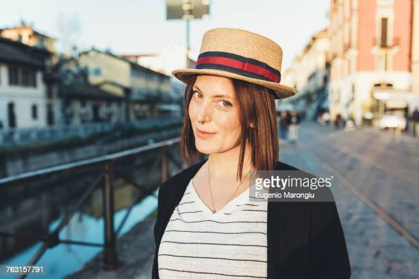 portrait of young woman in straw boater by canal - straw boater hat stock pictures, royalty-free photos & images