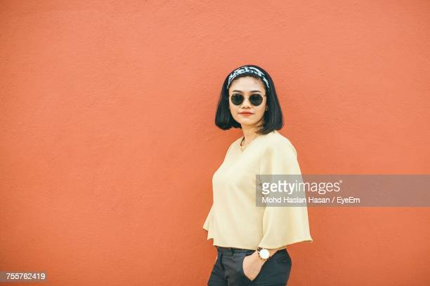 portrait of young woman in sunglasses standing against wall - headband stock pictures, royalty-free photos & images