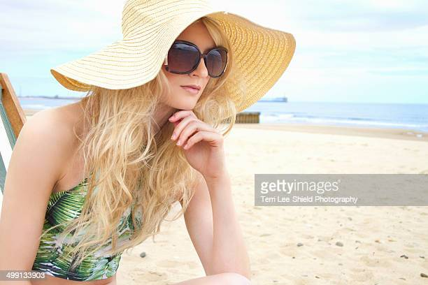 portrait of young woman in sunhat and sunglasses at beach - blyth northumberland stock pictures, royalty-free photos & images