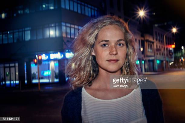 Portrait of young woman in the city at night