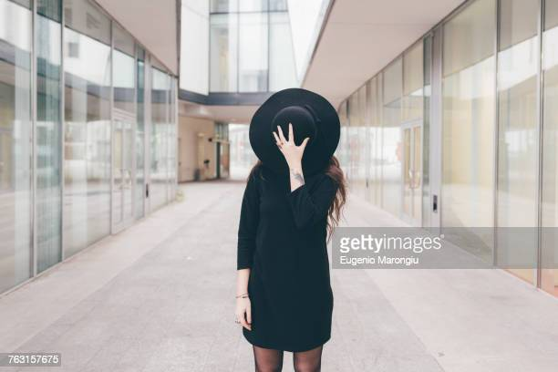 portrait of young woman in urban environment, covering face with hat - se cacher photos et images de collection