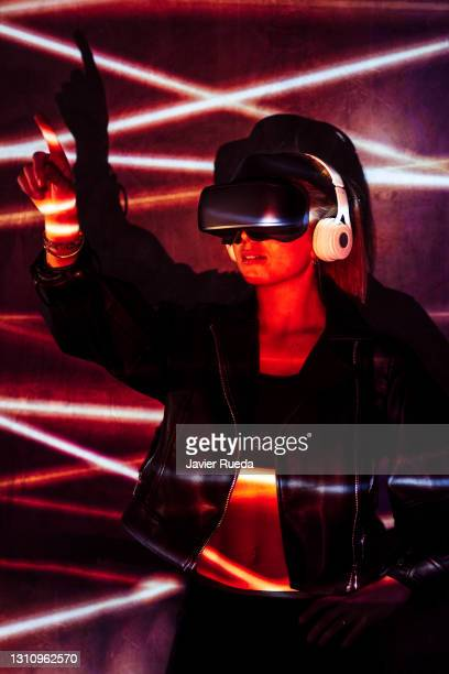 portrait of young woman in vr glasses, playing video games simulation, trying to touch something with her finger - google stock pictures, royalty-free photos & images