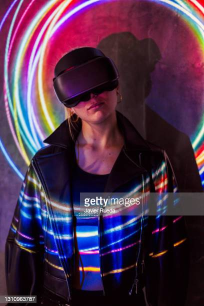 portrait of young woman in vr glasses standing against projection screen. she is looking at something in her googles. she is lighted with colorful spiral neon lights. - google stock pictures, royalty-free photos & images
