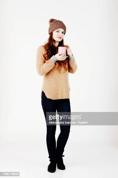 Portrait Of Young Woman In Warm Clothing Holding Coffee Mug Against White Background