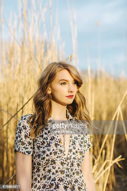 Portrait of young woman in wheat field, looking away