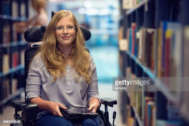 portrait of young woman in wheelchair in library - accessibility stock pictures, royalty-free photos & images