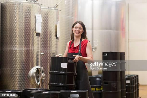 portrait of young woman in wine cellar next to fermentation tanks, smiling - sigrid gombert stock-fotos und bilder