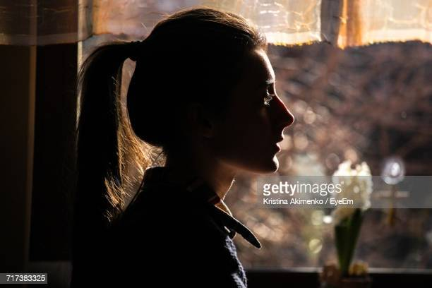 portrait of young woman indoors - back lit stock pictures, royalty-free photos & images