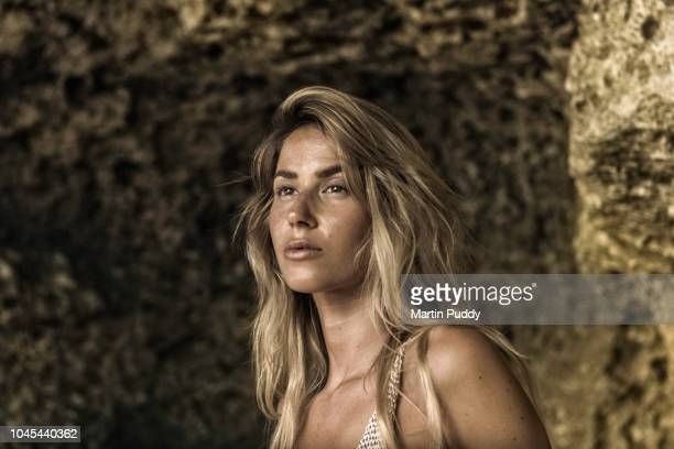 portrait of young woman inside a cave on the beach
