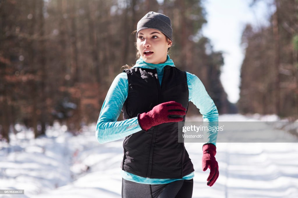 Portrait of young woman jogging in winter forest : Stock Photo